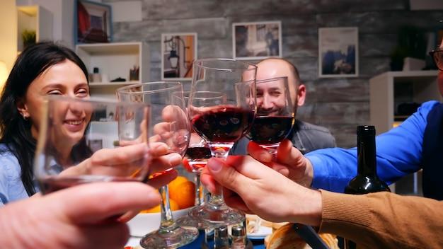 テーブルの上で夕食時に赤ワインのグラスをチリンと鳴らす家族のショットを拡大します。