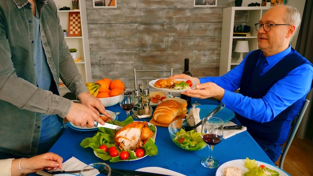 家族の夕食で父親に鶏肉を提供している男性のショットを拡大します。