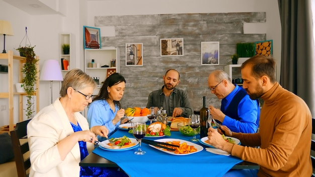 夕食時においしい食事を楽しんでいる家族のショットをズームアウトします。