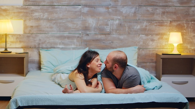 Zoom nel colpo di coppia allegra che indossa il pigiama. moglie sorridente.