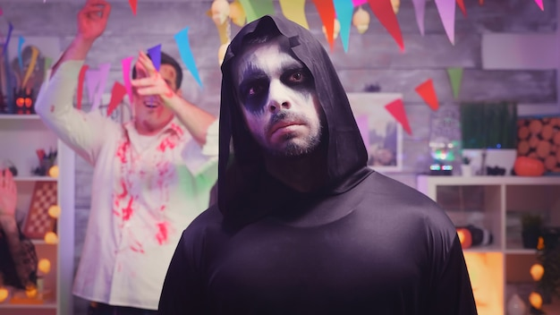 Zoom in shot of grim reaper at halloween party with his spooky friends dancing and having fun in the background