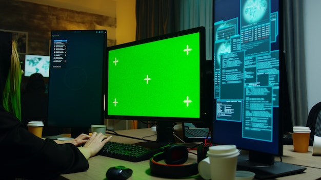Zoom in shot of hacker girl in front of computer with green screen. cyber criminal with hoodie.