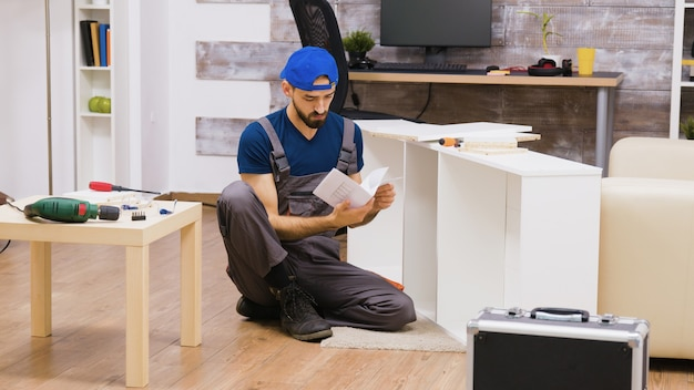 Zoom in shot of man in overalls assembles a shelf and reading instruction.