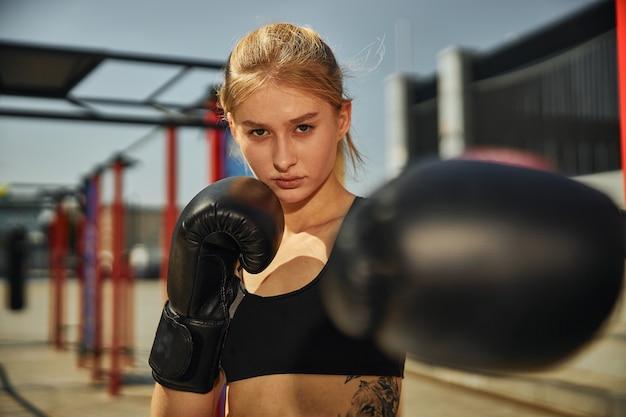 スポーツの成長でキックボクシングを訓練している魅力的な若い女性のボクシンググローブの左側の拡大図