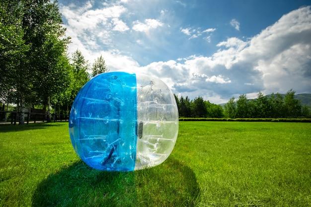 夏の芝生のゾーブバルーン。膨脹可能なゾーブボール屋外。コピースペースのあるレジャー活動のコンセプト。