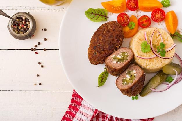 Котлеты из зразы с мясным фаршем, маринованным огурцом и яйцом с гарниром из булгура