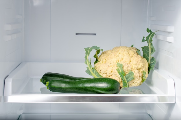 Кабачки и цветная капуста на полке в холодильнике.