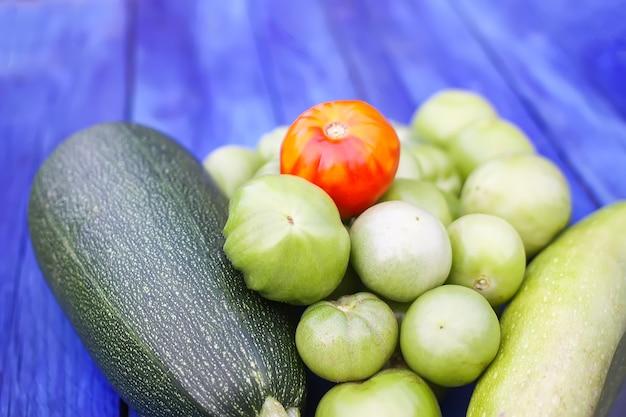 Кабачки и недозрелые помидоры. свежие сырые органические овощи на деревянных досках на открытом воздухе.