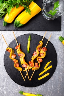 Zucchini and chicken kebab on wooden stick on black stone slate plate and grey surface,