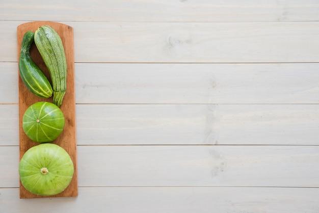 ズッキーニ;きゅうりとまな板の上の白い木製の机の上のひょうたん