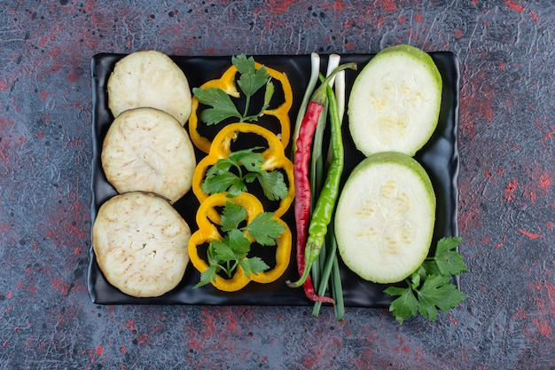 Zucchini, eggplant and bell pepper slices with hot peppers and spring onions on a platter on dark colored background. high quality photo
