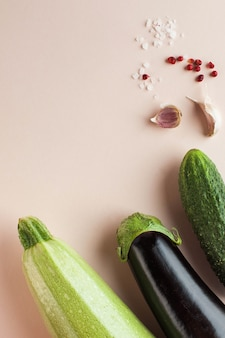 Zucchini eggplant and cucumber on a pink background minimalism concept of harvesting farming vegetab... Premium Photo