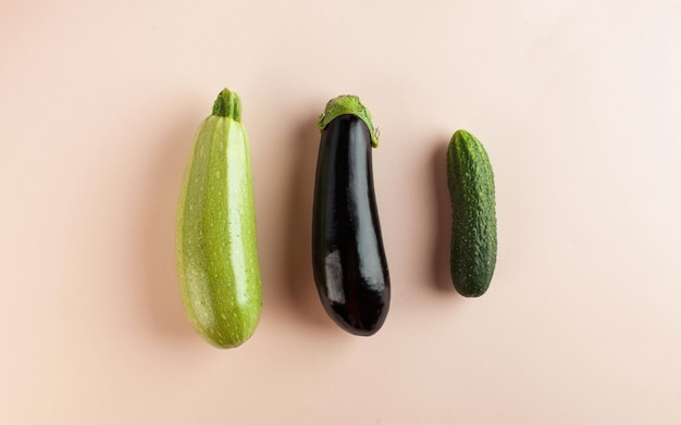 Zucchini eggplant and cucumber on a pink background minimalism concept of harvesting farming vegetables Premium Photo