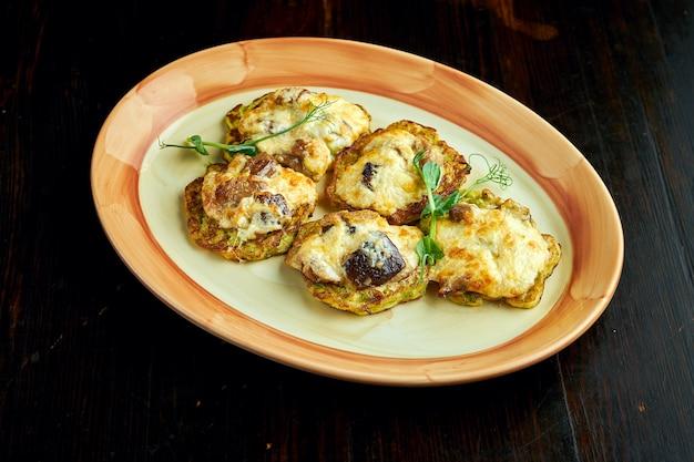 Блинчики из кабачков с запеченным сыром и грибами, подаются в тарелке