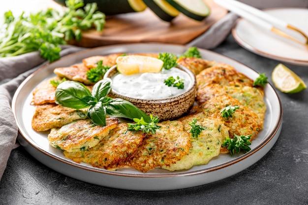 접시 클로즈업 채식 요리에 허브와 사워 크림을 곁들인 호박 팬케이크