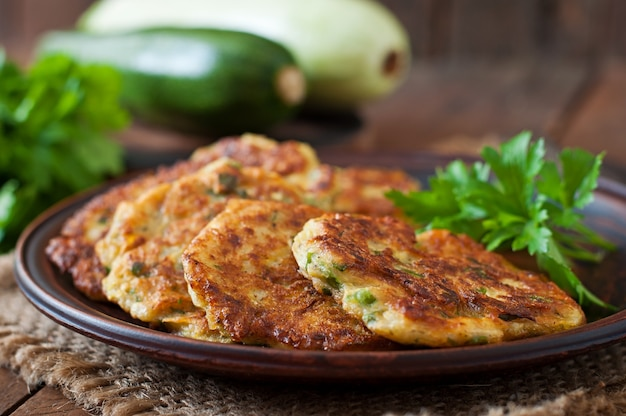 Zucchini pancakes with parsley on a wooden table