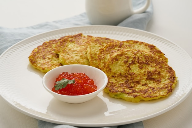 Zucchini pancakes with potato and red caviar, fodmap keto diet side view closeup