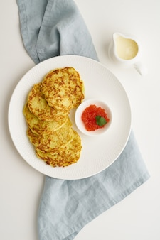 Zucchini pancakes with potato and red caviar, fodmap keto diet top view