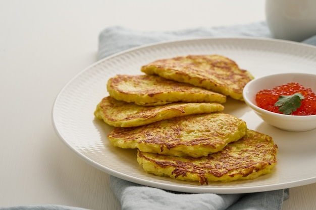 Zucchini pancakes with potato and red caviar