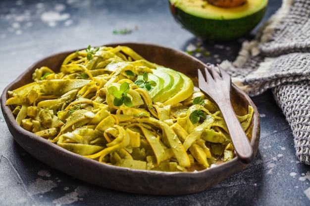 Zucchini pasta with pesto and avocado in dark dish. healthy vegan food.