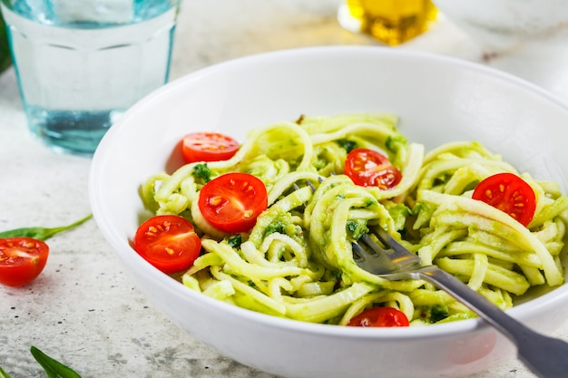 Zucchini pasta with pesto, avocado and tomatoes in white plate. raw vegan food concept.
