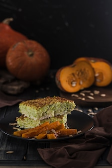 Zucchini pie with baked pumpkin on dark wooden copyspace close-up with copyspace.