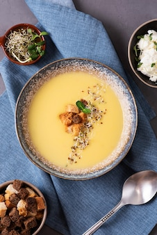 Zucchini and pumpkin puree soup decorated with croutons and microgreens, vegetarian cream soup on a gray background.