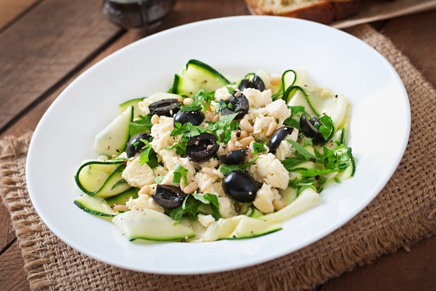 Zucchini salad with feta, olives and pine nuts