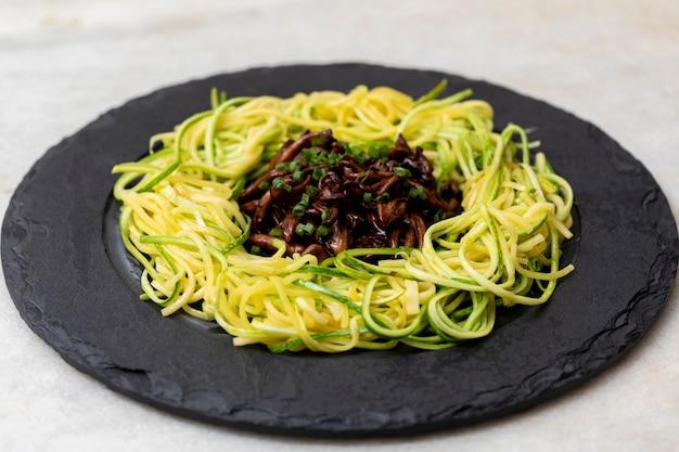 黒い石のプレートにしめじを添えたズッキーニのスパゲッティ。