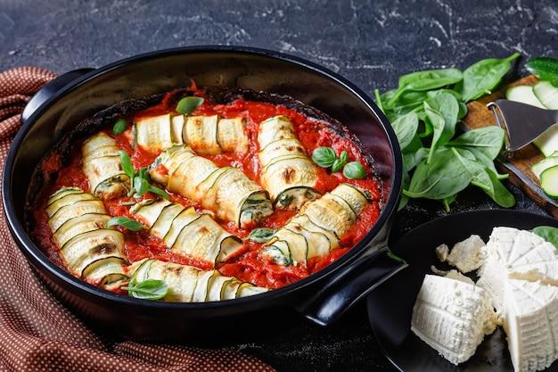 아기 시금치와 섞인 리코 타를 채우는 호박 스트립, 신선한 바질은 토마토 소스에 구운 상태로 어두운 콘크리트 테이블에 둥근 검은 베이킹 접시에 제공됩니다.