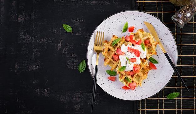 Вафли из кабачков, оладьи из кабачков, приготовленные на вафельнице, вегетарианские вафли из кабачков с помидорами, сметаной и базиликом в белой тарелке. вид сверху, плоская планировка