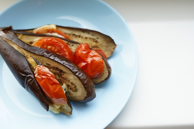 Zucchini with cheese and tomato on blue plate