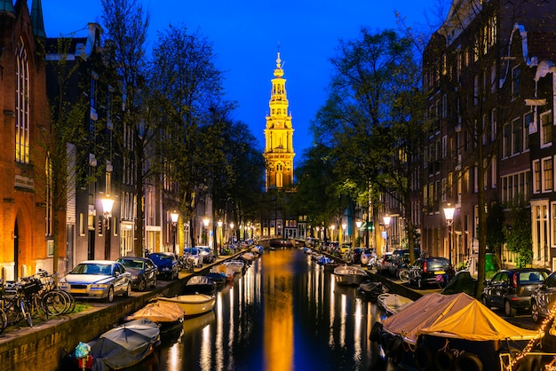 夜にオランダ、アムステルダムの街の運河の終わりにアムステルダムzuiderkerk教会の塔。