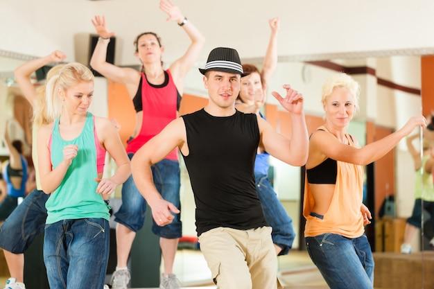 Zumba или jazzdance - молодые люди танцуют в студии
