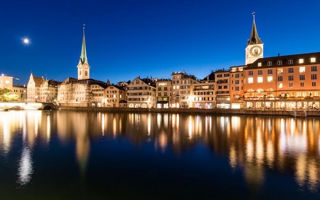 Цюрихский горизонт с церковью святого петра вдоль реки лиммат в сумерках