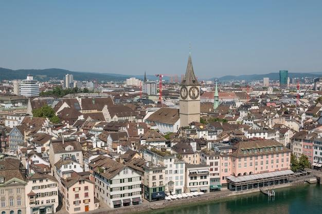 취리히, 스위스 - 2017년 6월 19일: 스위스 그로스뮌스터 교회에서 유명한 프라우뮌스터 교회와 리마트 강이 있는 역사적인 취리히 도심의 공중 전망. 여름의 화창한 날
