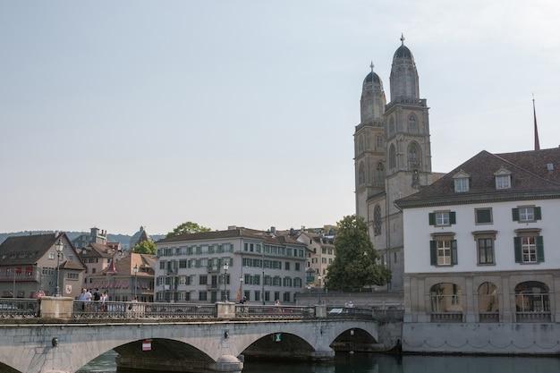 취리히, 스위스 - 2017년 6월 19일: 유명한 그로스뮌스터 교회와 리마트 강이 있는 역사적인 취리히 도심의 탁 트인 전망. 여름 풍경, 햇살 날씨, 푸른 하늘과 화창한 날