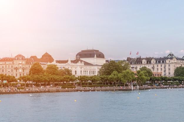 취리히, 스위스 - 2017년 6월 21일: 취리히 호수와 멀리 오페라 하우스에서 볼 수 있습니다. 화창한 날씨, 극적인 푸른 하늘. 화려한 여름날, 저녁 팀