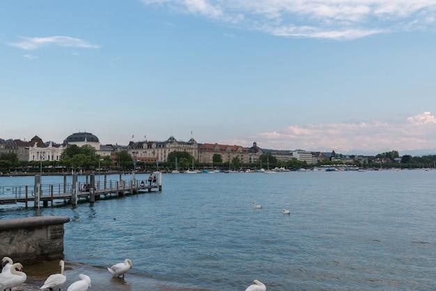 취리히, 스위스 - 2017년 6월 21일: 취리히 호수와 멀리 오페라 하우스, 취리히, 스위스, 유럽에서 볼 수 있습니다. 화창한 날씨, 극적인 푸른 하늘. 화려한 여름날, 저녁 팀