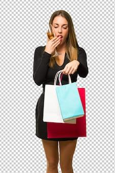 新しい年2019を祝うシャンパンを持つ女性は、ショッピングバッグをたくさん持っていると驚いた