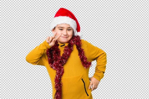 サンタの帽子をかぶっているクリスマスの日を祝う少年は、指で2番を示します。