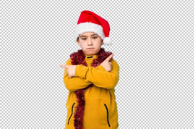 サンタ帽子をかぶったクリスマスの日を祝う小さな男の子は横向きにポイントし、2つのオプションから選択しようとしています。