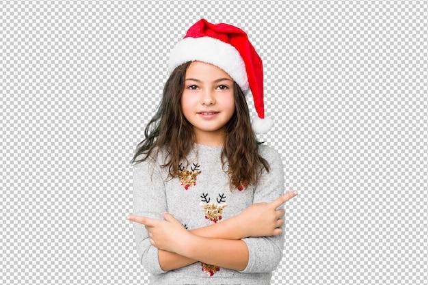 クリスマスを祝う少女は横向きのポイントをポイントし、2つのオプションから選択しようとしています。