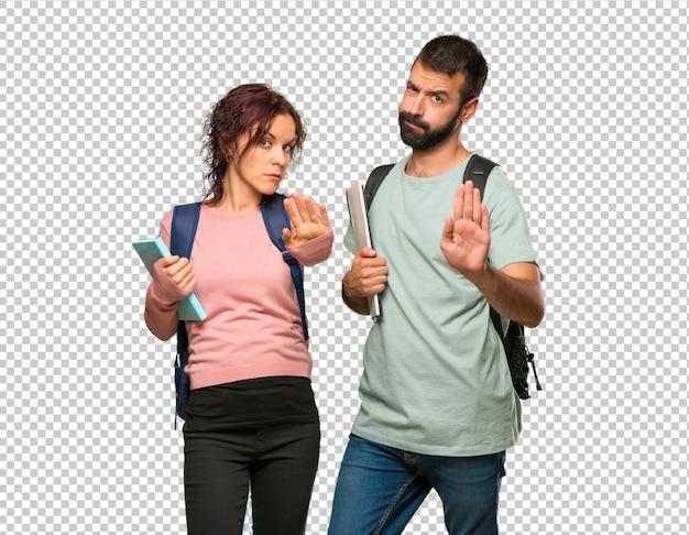 バックパックと本を持っている2人の学生が、間違った考えを否定する彼女の手でストップジェスチャーを作る