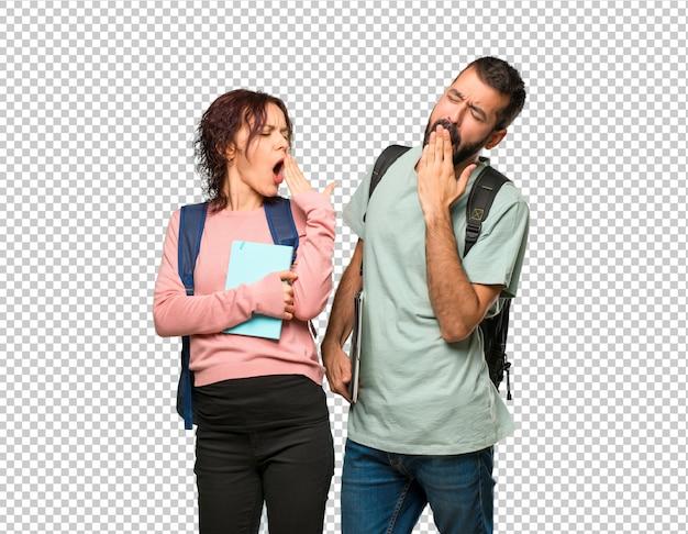 バックパックとあくびと手で口を覆っている本を持つ2人の学生