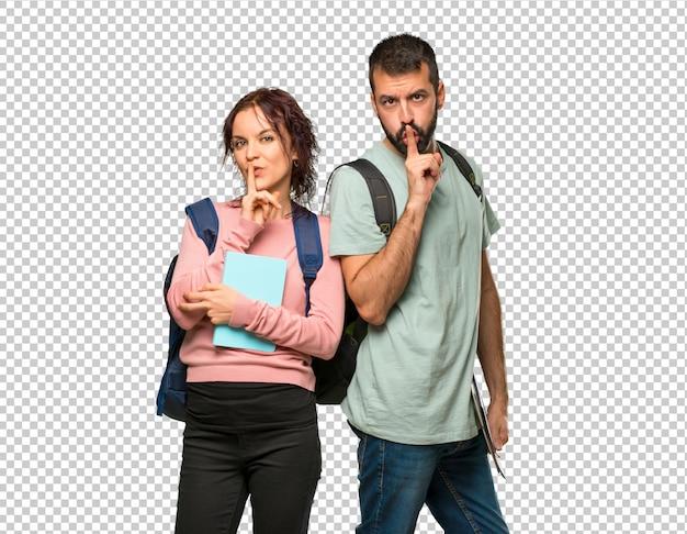 バックパックと口を閉じるサインと沈黙のジェスチャーを示す本を持つ2人の学生