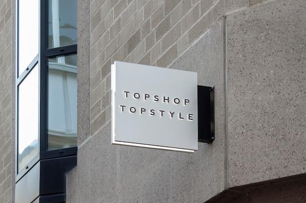 壁に掛かっている屋外通り都市白い正方形3 dロゴ記号のモックアップ