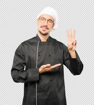 3番目のジェスチャーを作る若いシェフ