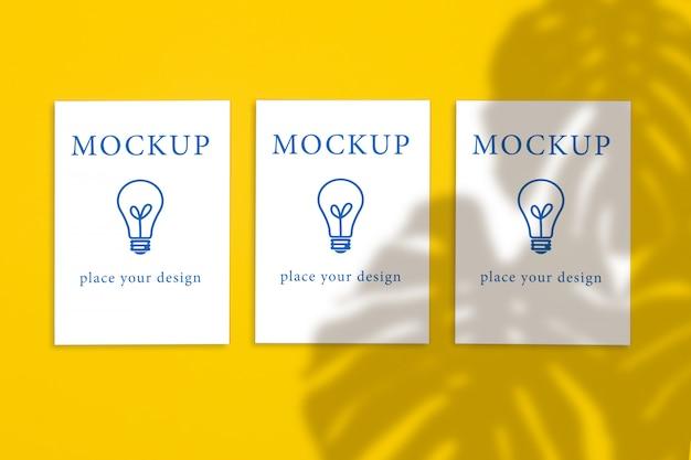 黄色の背景、モックアップに3つの縦のポストカードのトップビュー