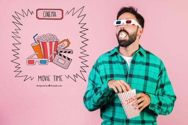 Бородатый молодой человек ест попкорн с 3-мя бокалами для кино рядом с нарисованными от руки элементами кино